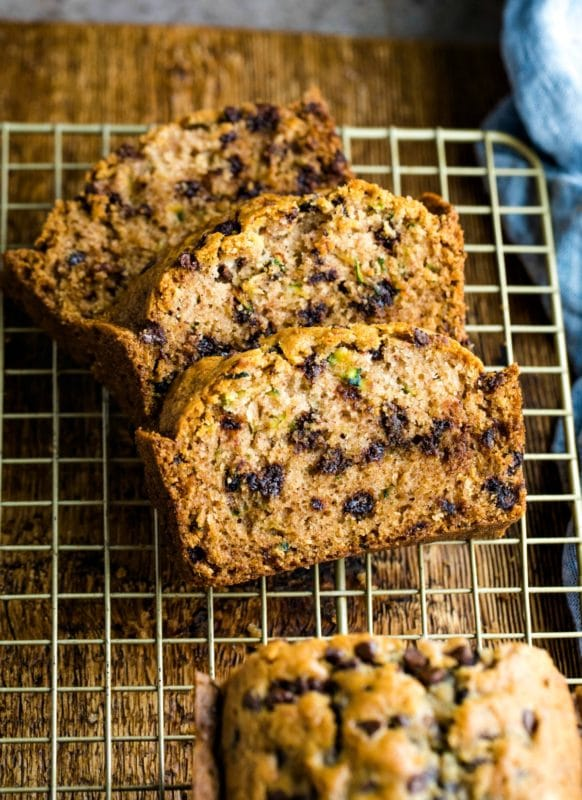 Three slices of chocolate chip zucchini bread on a gold wire cooling rack