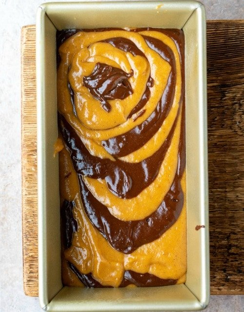 Chocolate marble pumpkin bread batter in a gold loaf pan