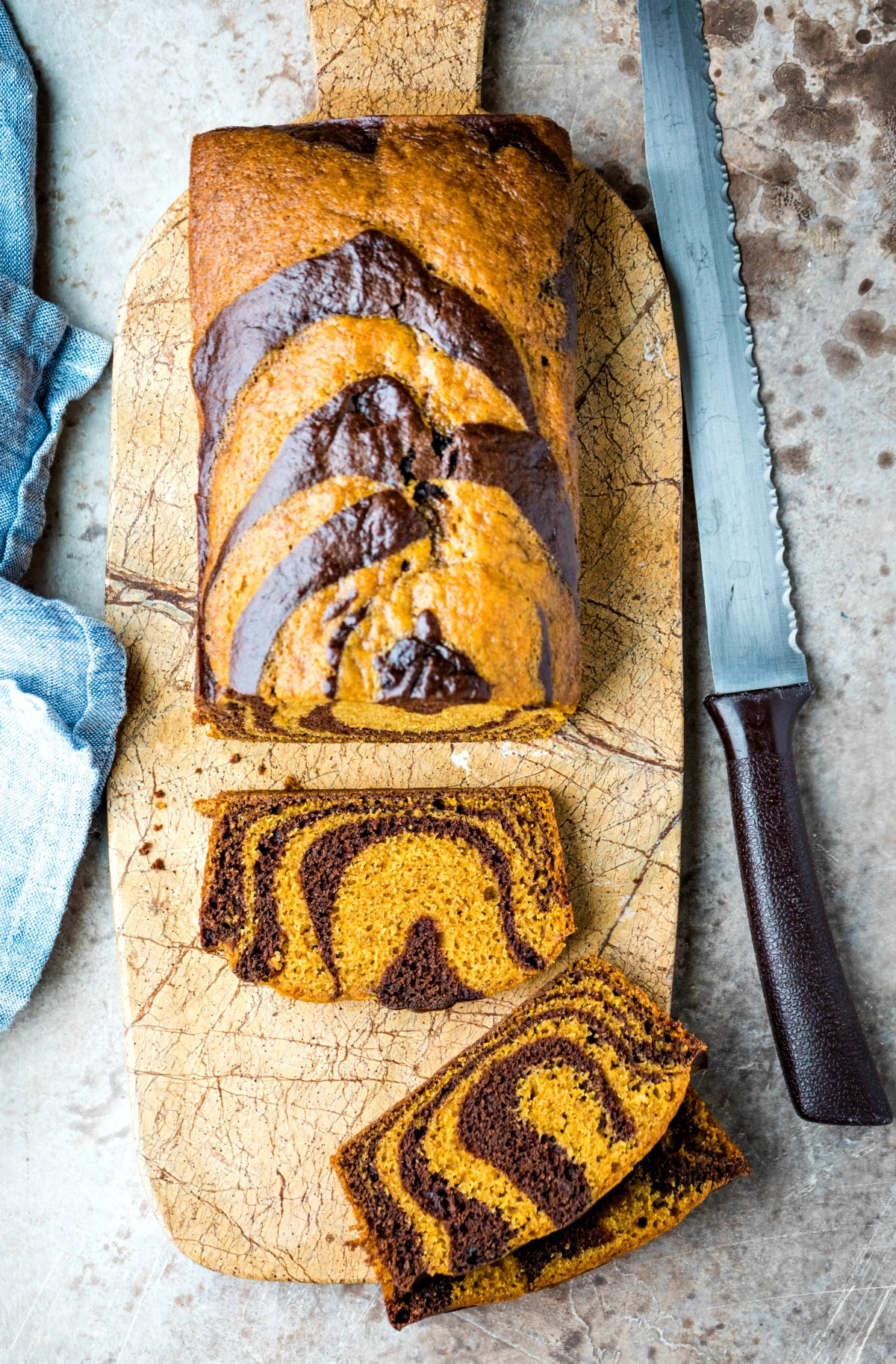 Loaf of chocolate marble pumpkin bread next to a bread knife