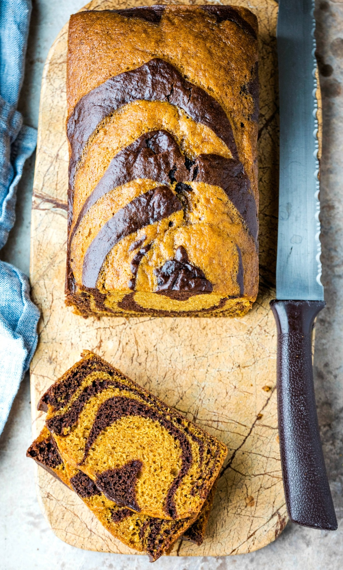 Two slices of chocolate marble pumpkin bread on a marble cutting board