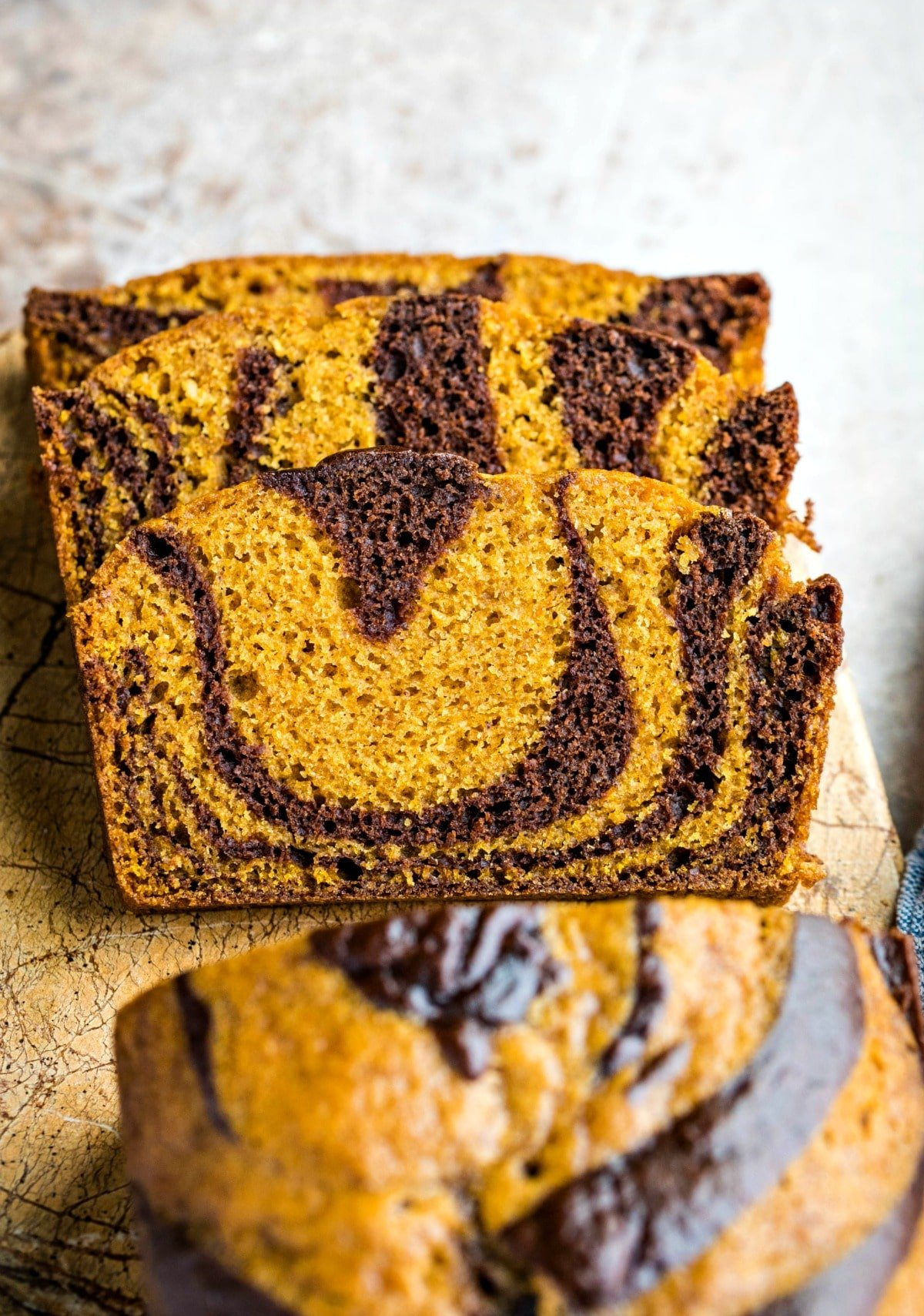 Three stacked slices of chocolate marble pumpkin bread