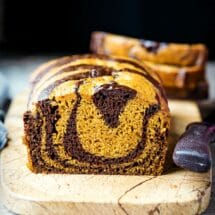 Loaf of chocolate marble pumpkin bread on a marble cutting board