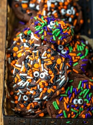 Halloween monster cookies in a black metal tin