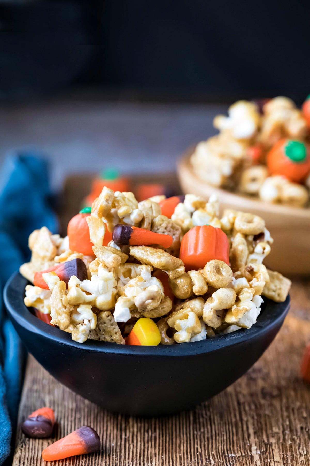 Halloween snack mix in a black wooden bowl on a wooden cutting board