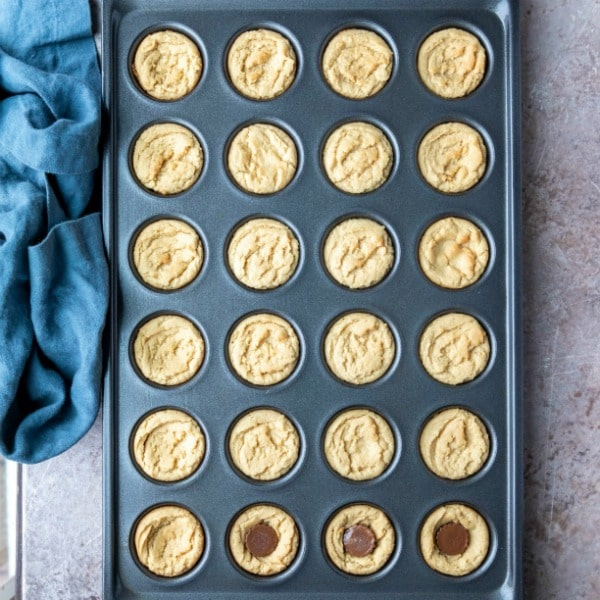 Baked peanut butter cup cookies with peanut butter cups in them.