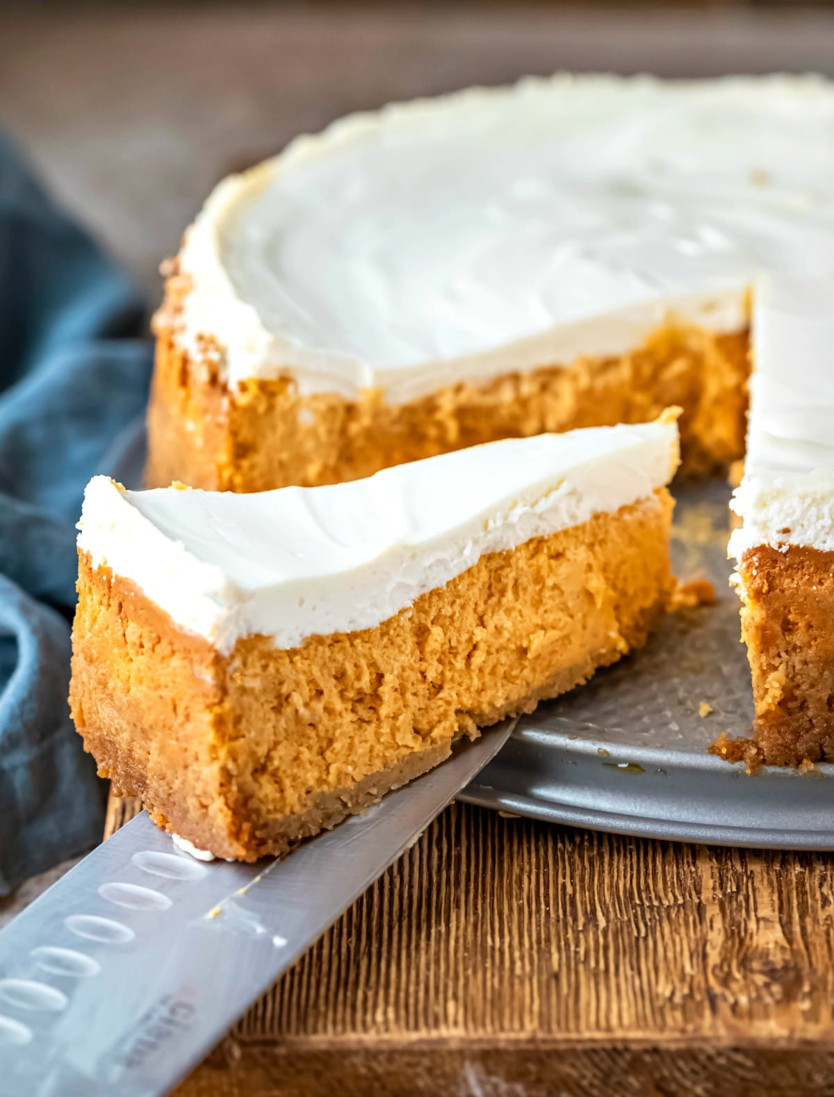 Slice of pumpkin cheesecake next to the entire cheesecake.