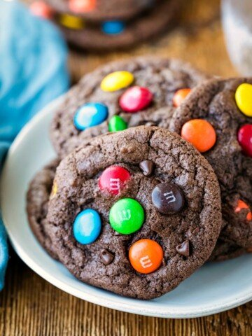 Chocolate M&M cookies stacked on a white plate.