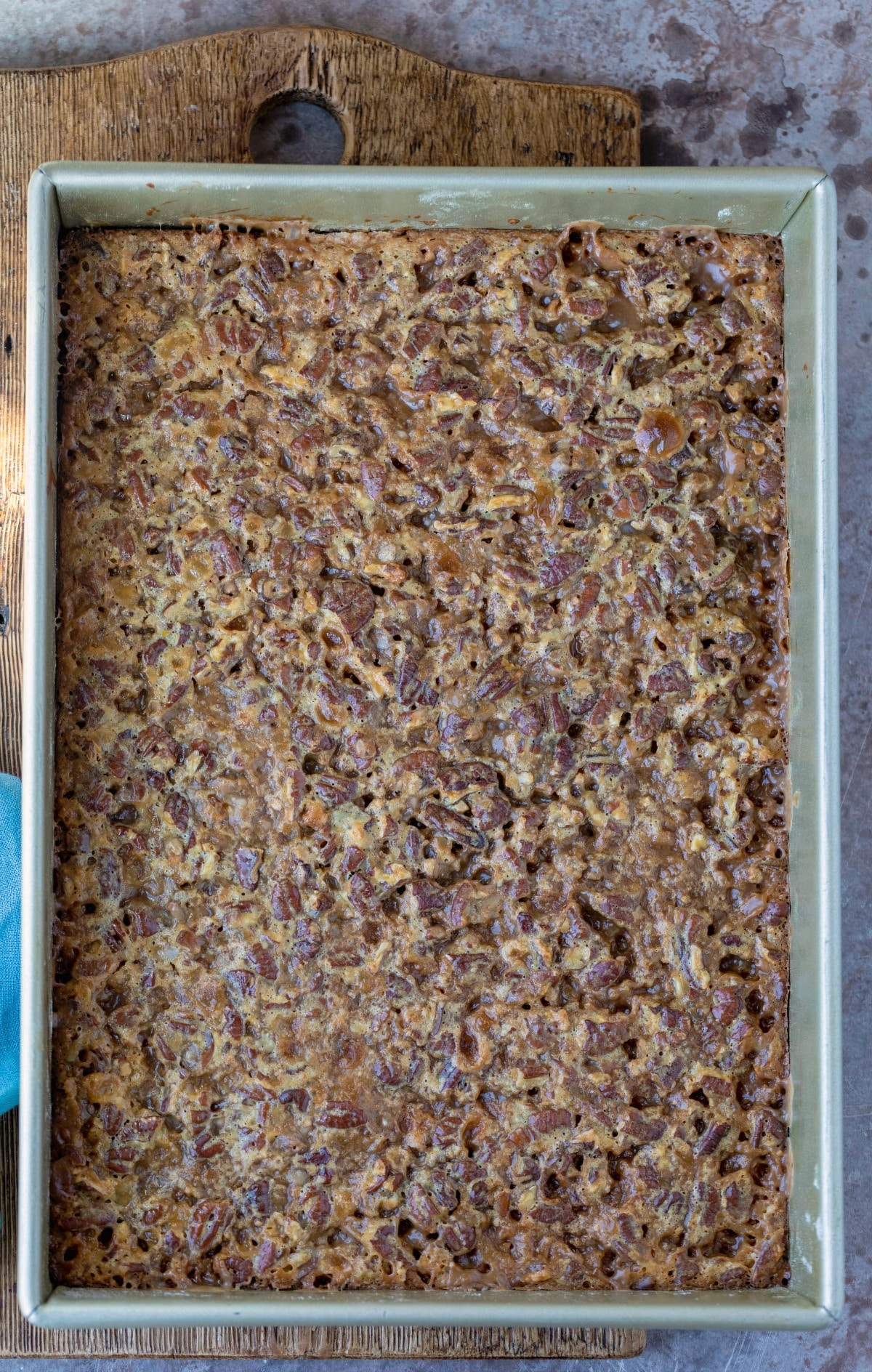 Baked toffee pecan pie bars in a gold baking pan