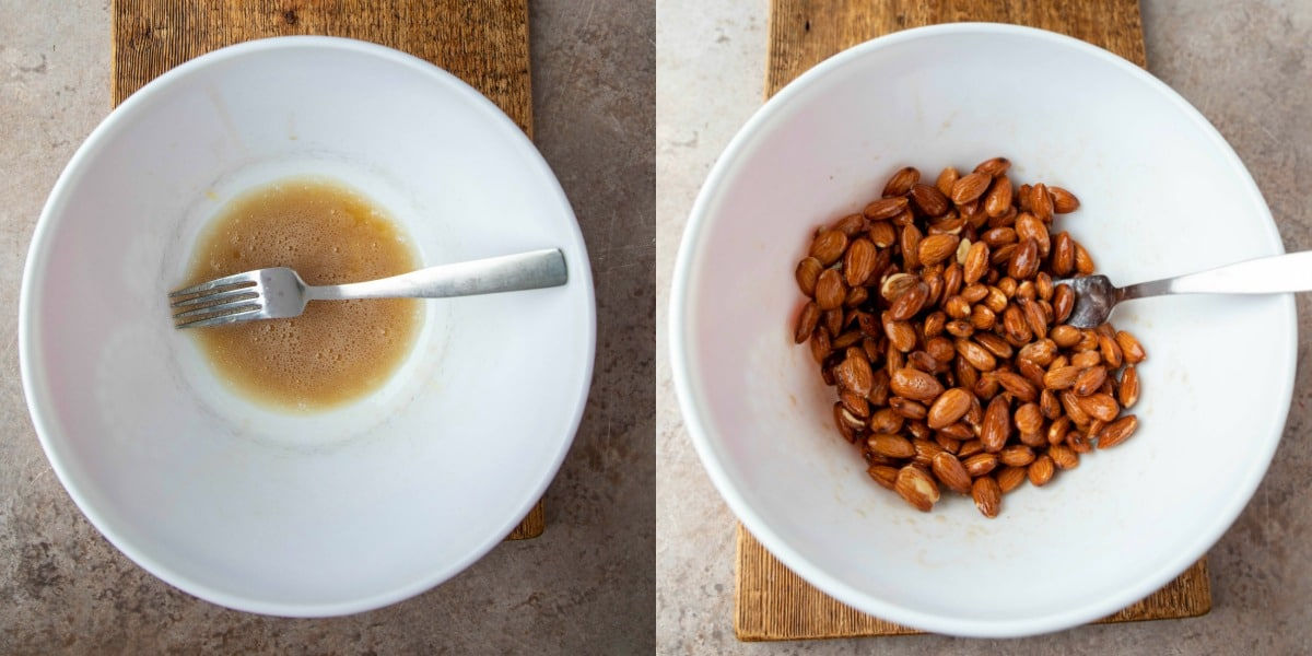 Almonds coated in beaten egg white mixture in a white mixing bowl