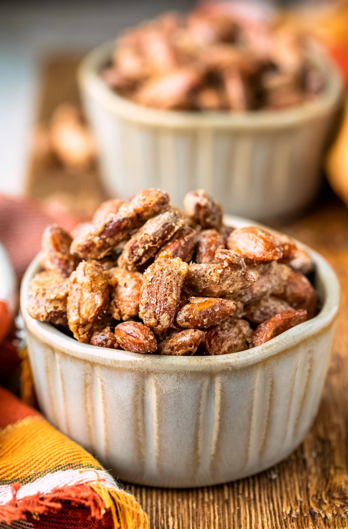 Two ramekins of cinnamon almonds on a wooden cutting board
