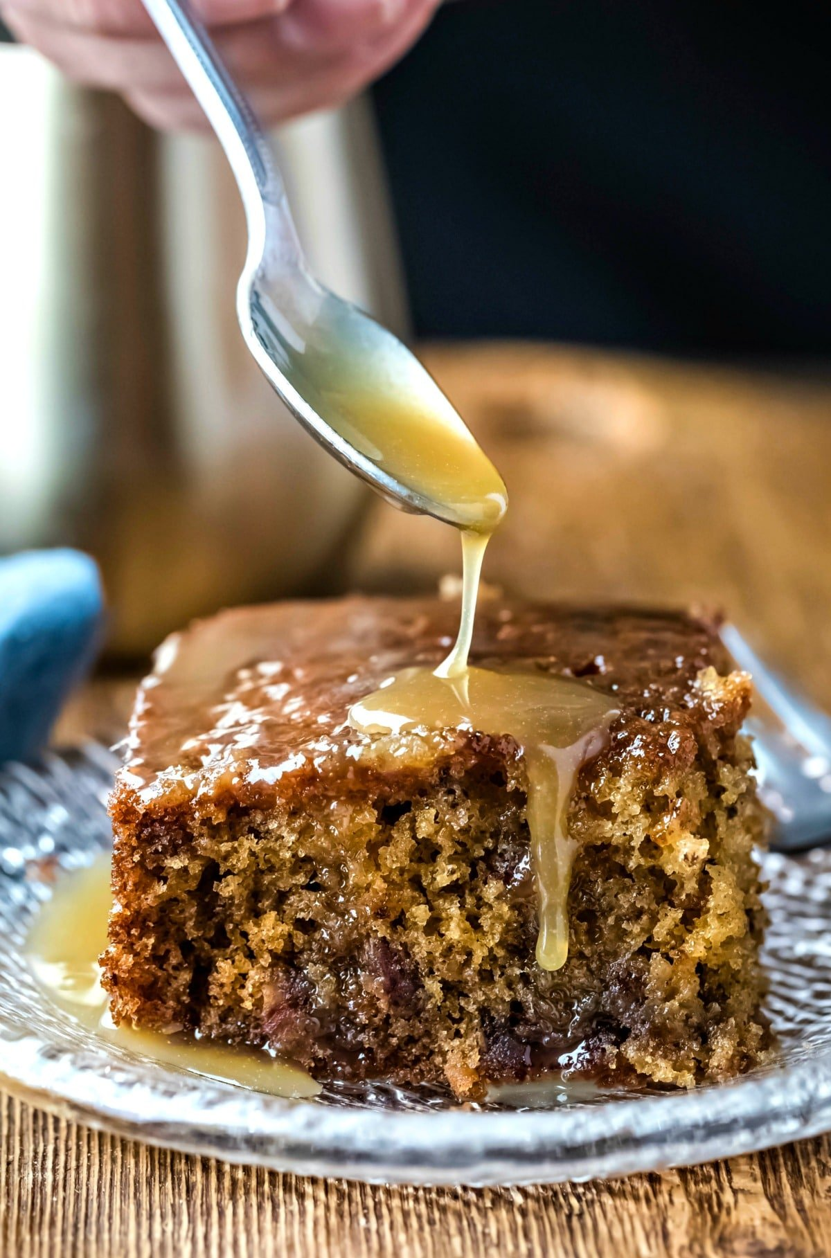 Spoon drizzling sauce onto a piece of sticky toffee pudding cake