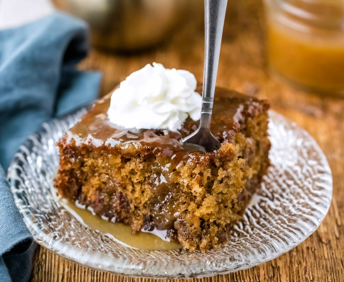 Slice of sticky toffee pudding cake with a silver fork in it