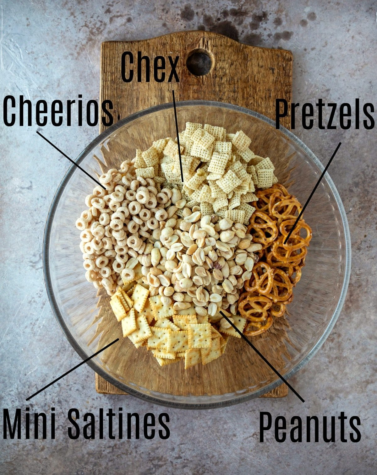 White chocolate party mix ingredients in a glass mixing bowl