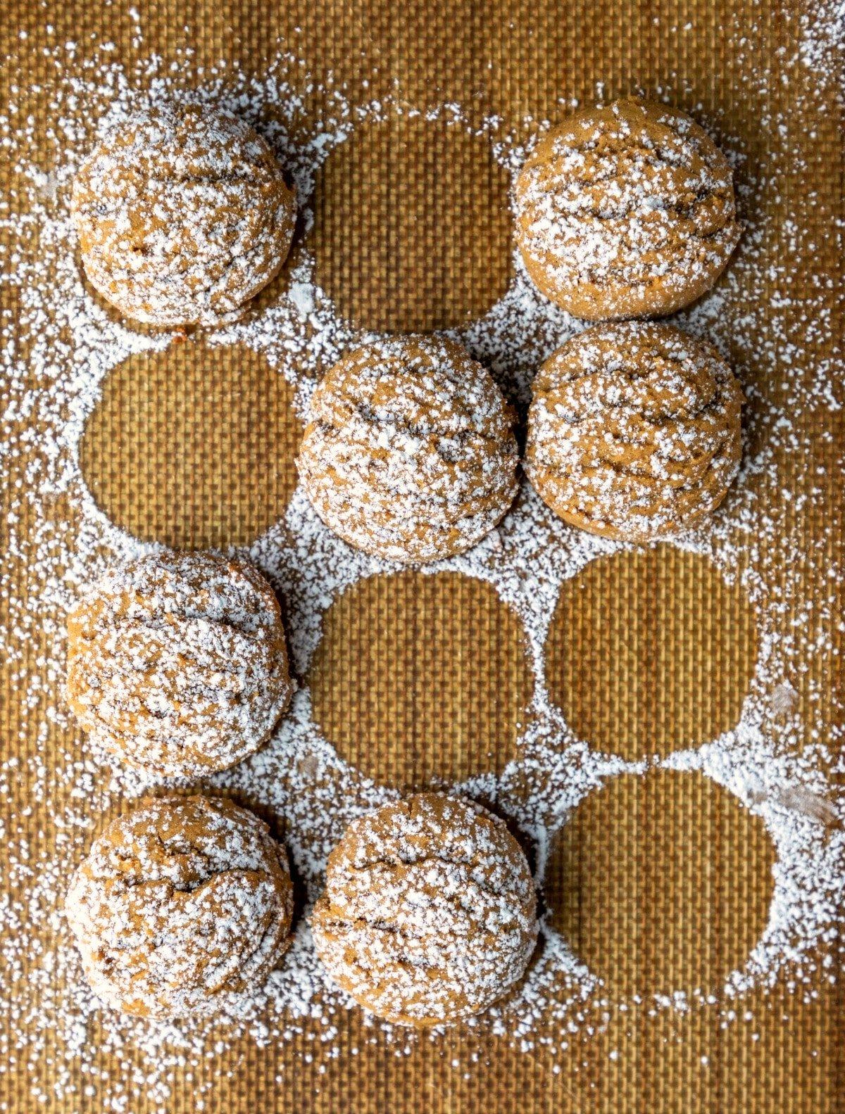 Pfeffernusse cookies sprinkled with powdered sugar on a baking mat