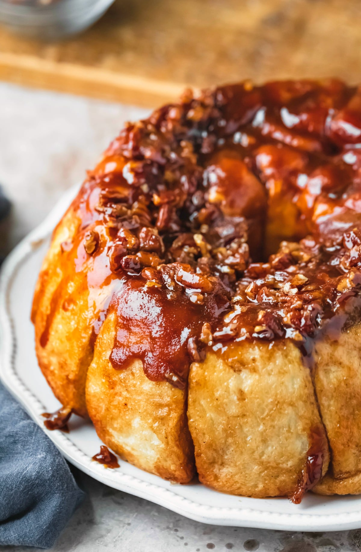 Overnight sticky buns next to a wooden cutting board and a bowl of pecans