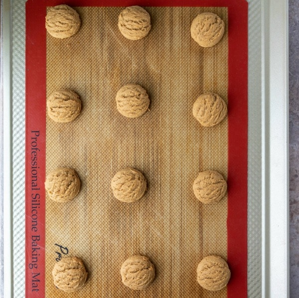 Baked pfeffernusse cookies on a silicone baking mat