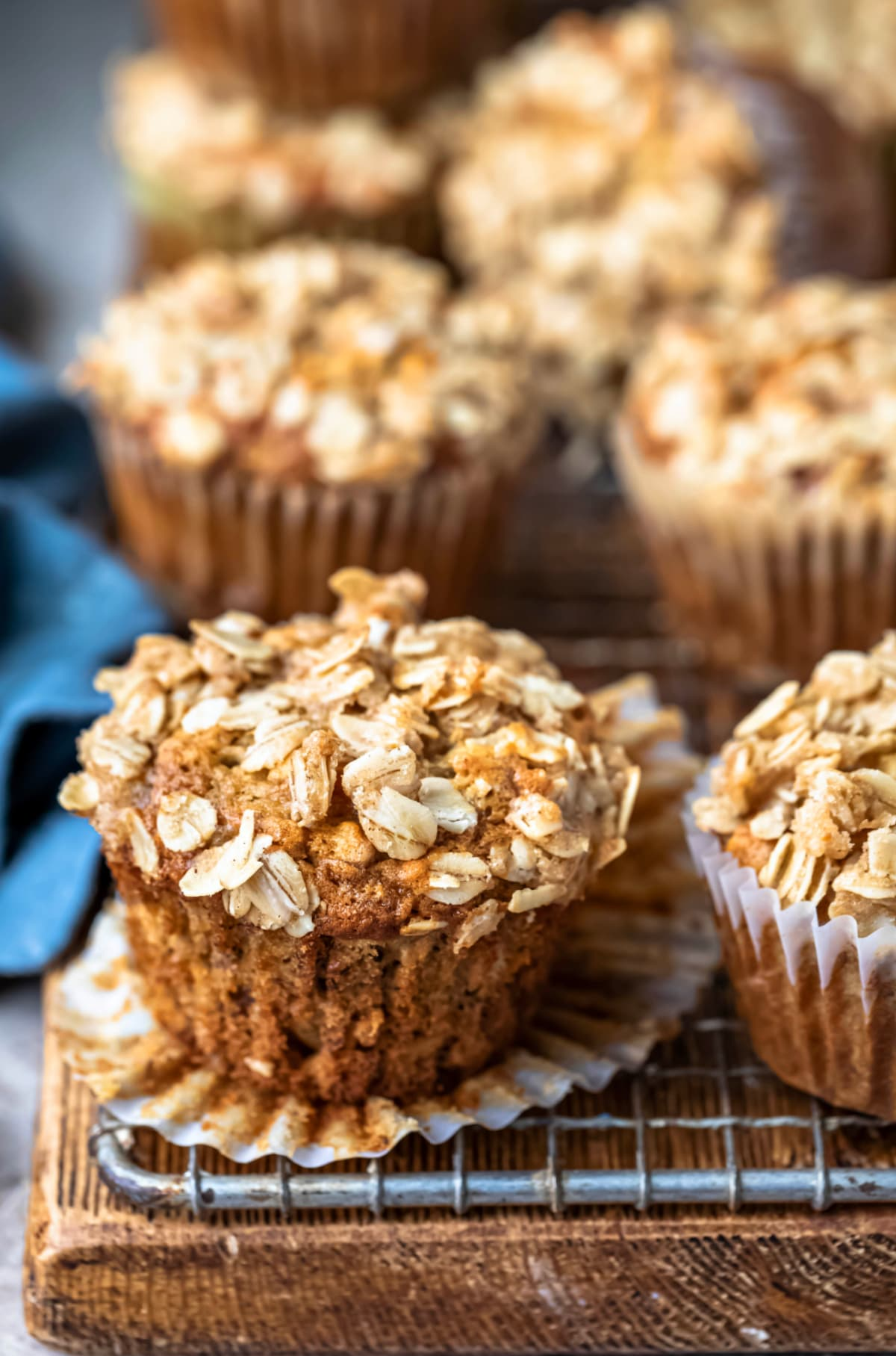 Unwrapped banana oatmeal muffin next to a blue linen napkin