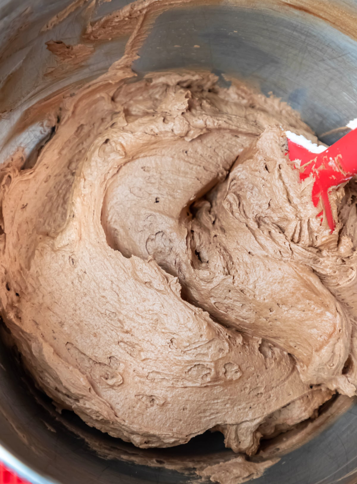 Chocolate buttercream frosting in a silver mixing bowl