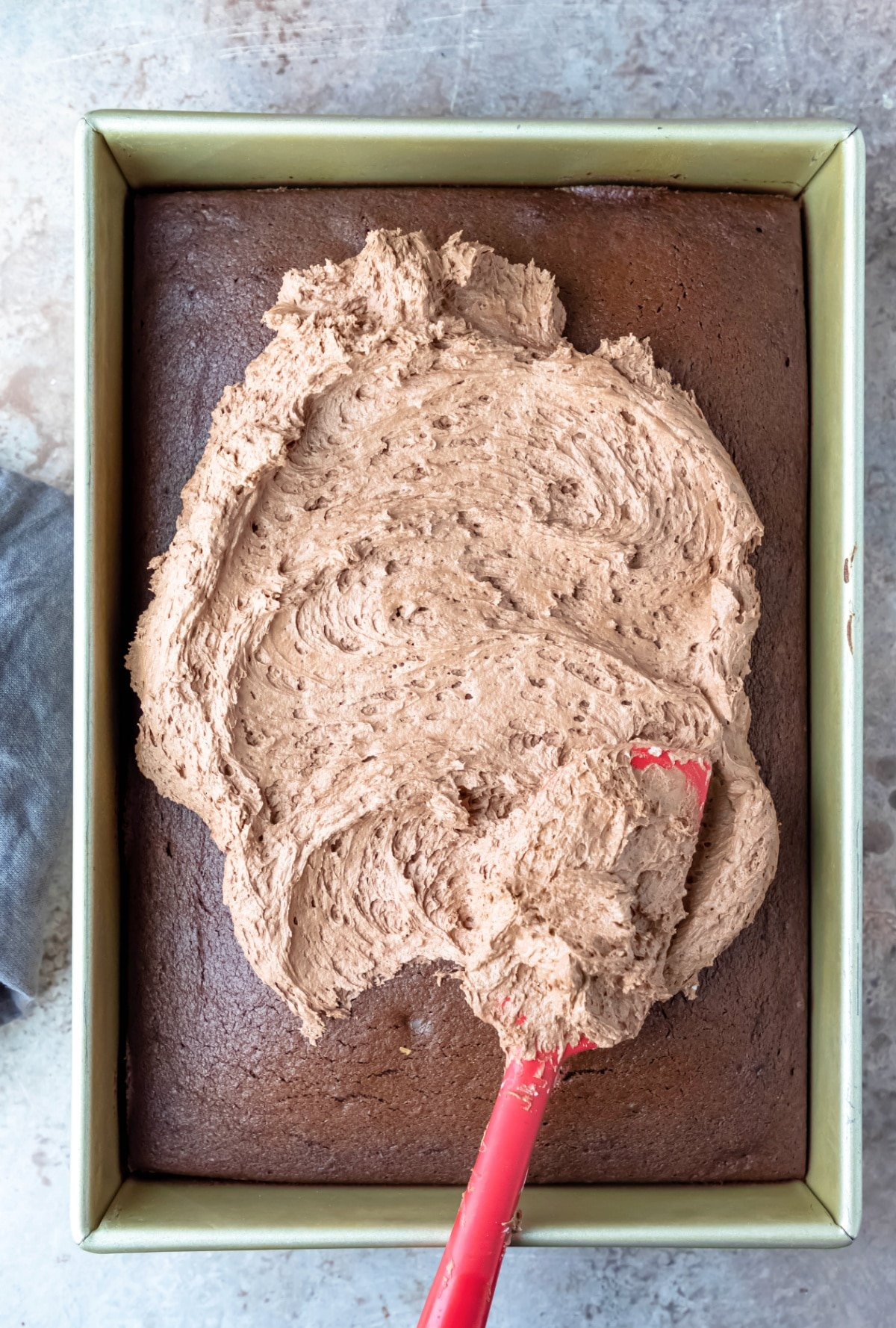 Red spatula spreading chocolate frosting on a cake