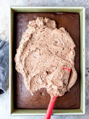 A spatula spreading melted chocolate buttercream on a chocolate cake