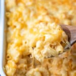 Wooden spoon scooping up baked mac and cheese