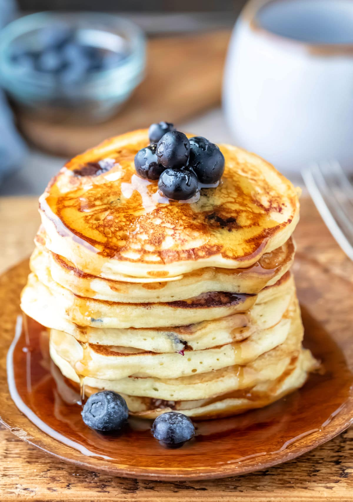 Stack of blueberry pancakes with maple syrup dripping off