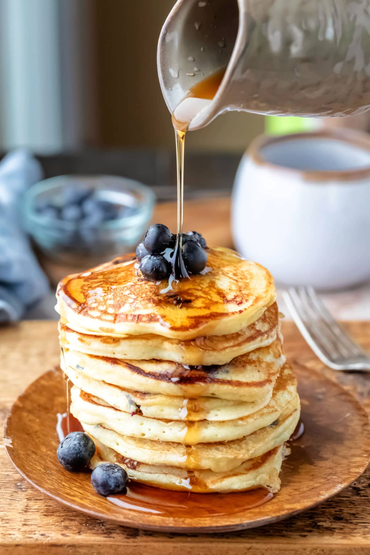 Maple syrup pouring onto a stack of blueberry lemon ricotta pancakes
