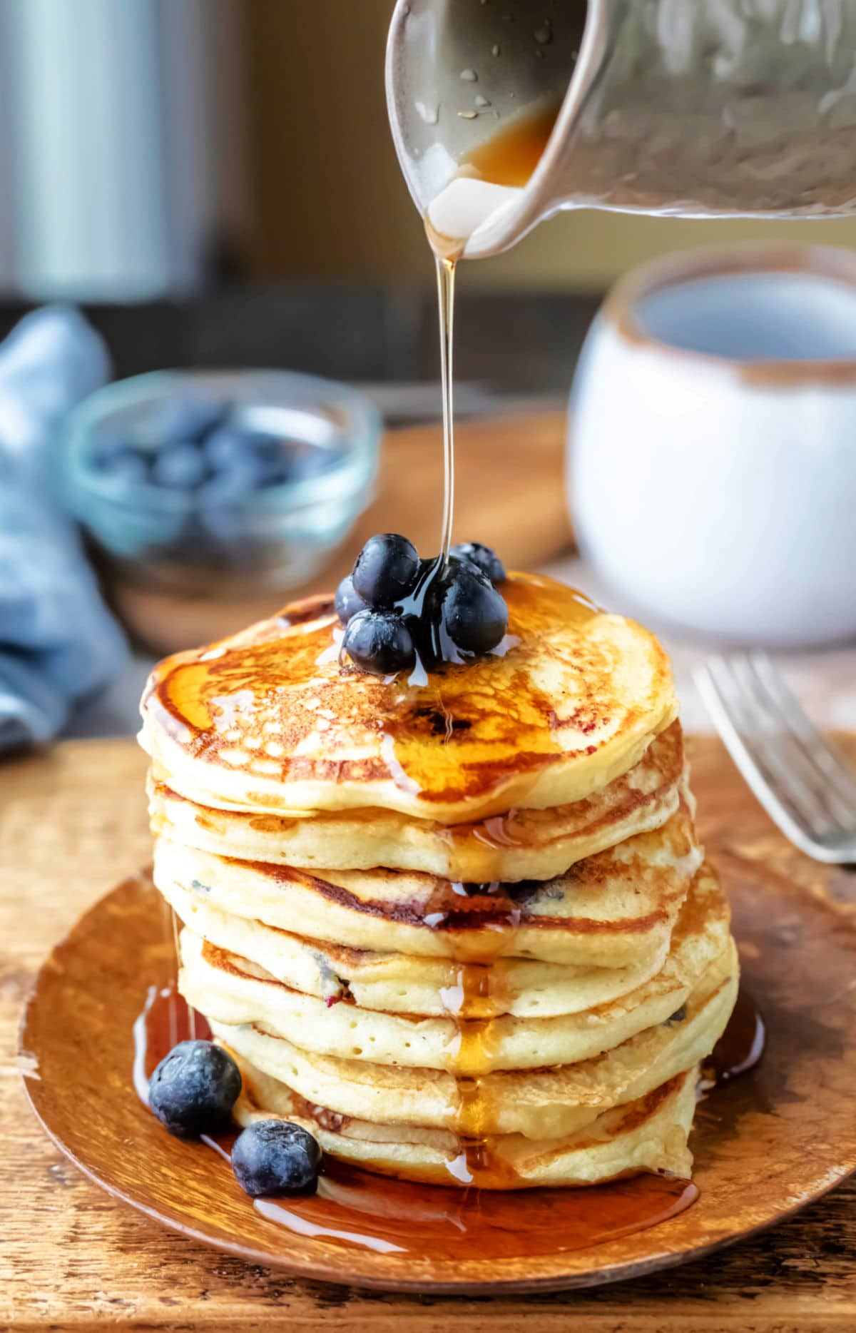 Pottery jug pouring maple syrup onto stack of pancakes