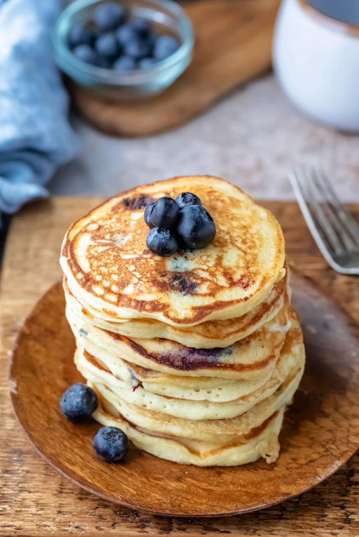 Stack of blueberry pancakes on a wooden plate