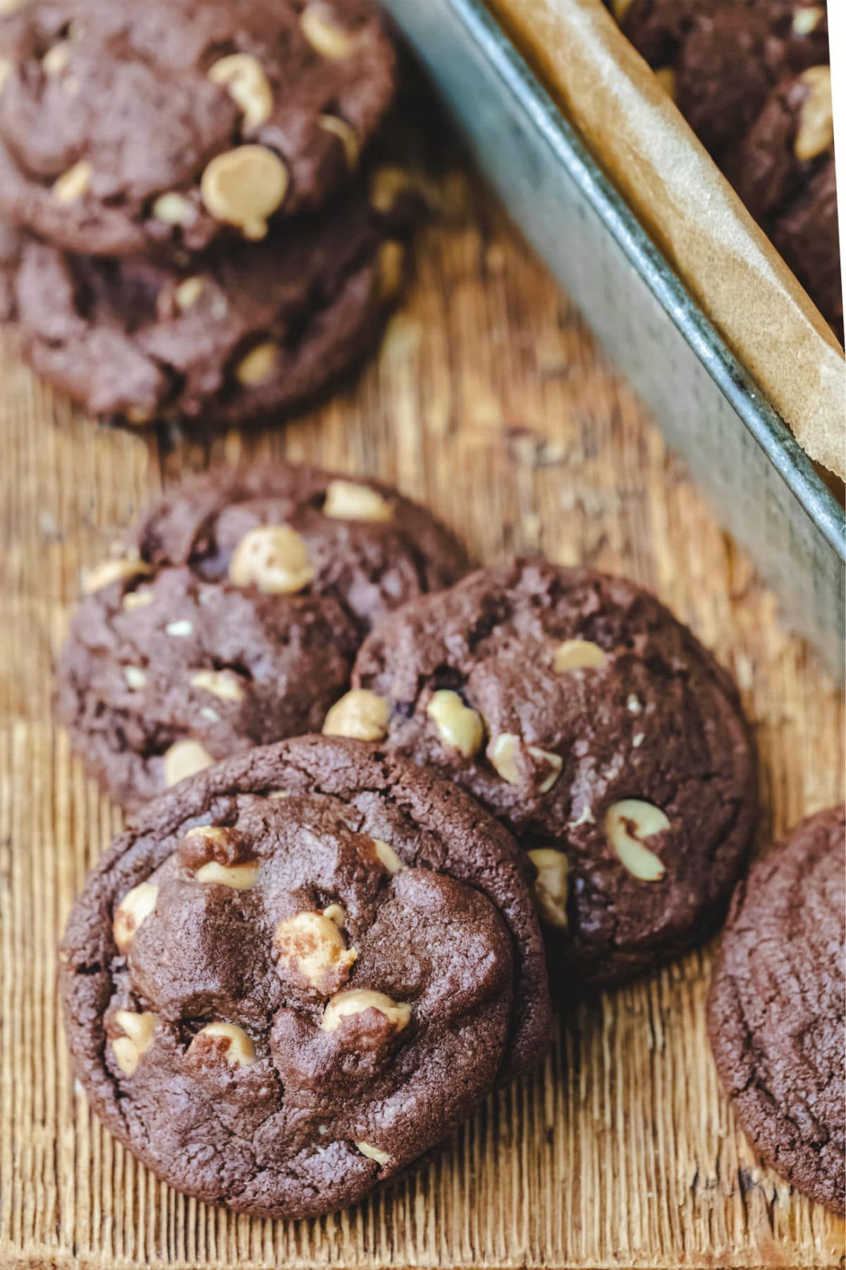 Chocolate peanut butter cookies next to a tin of cookies