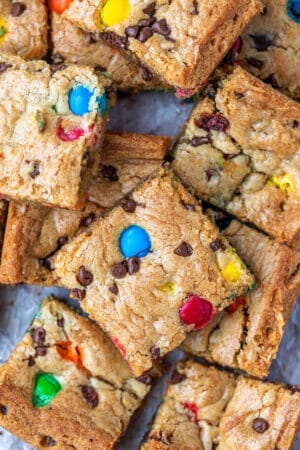 Stack of M&M cookie bars on a piece of parchment paper
