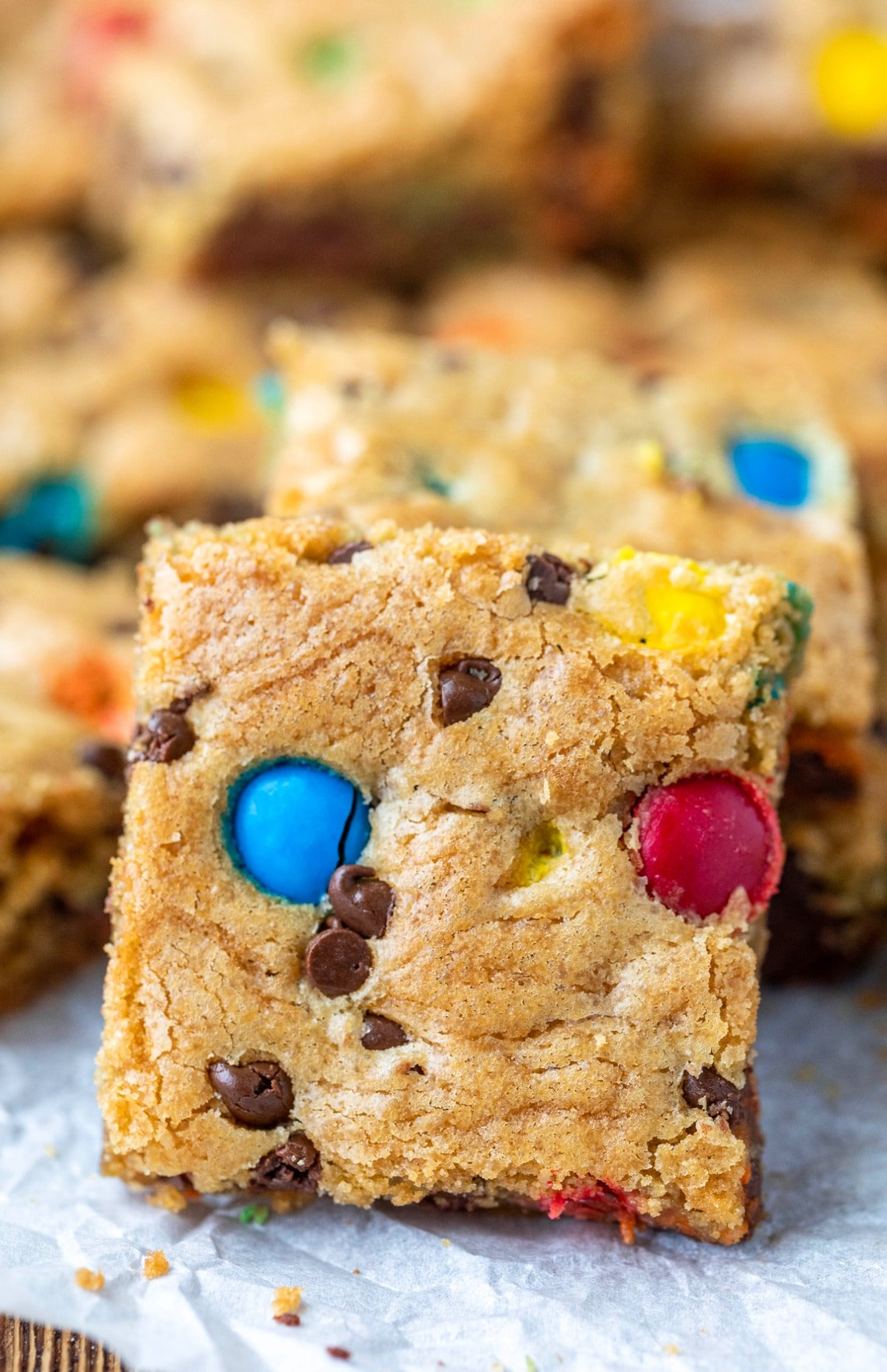 M&M cookie bar standing up next to a stack of cookie bars
