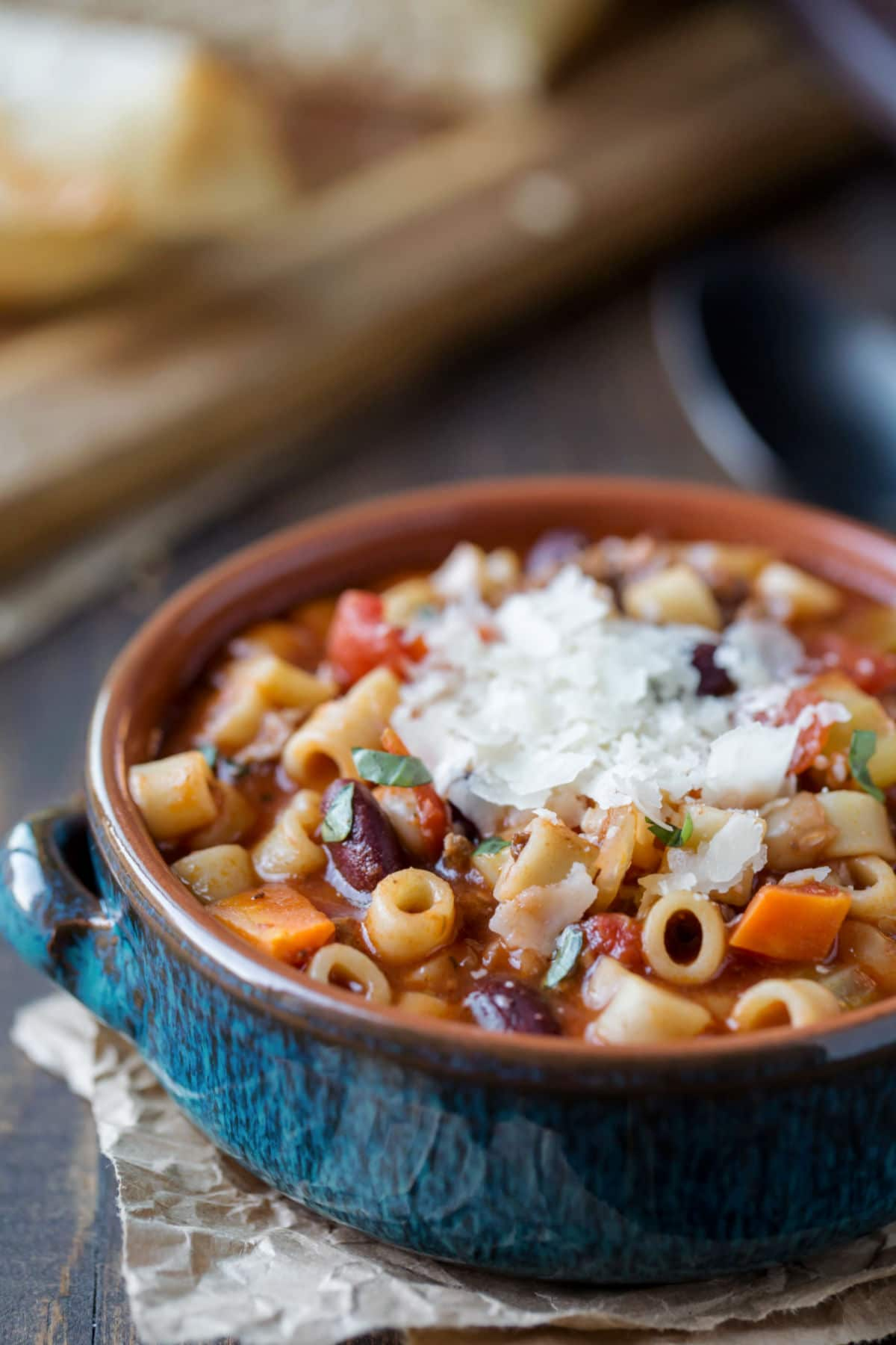 Pasta e Fagioli Soup topped with parmesan cheese in a blue bowl