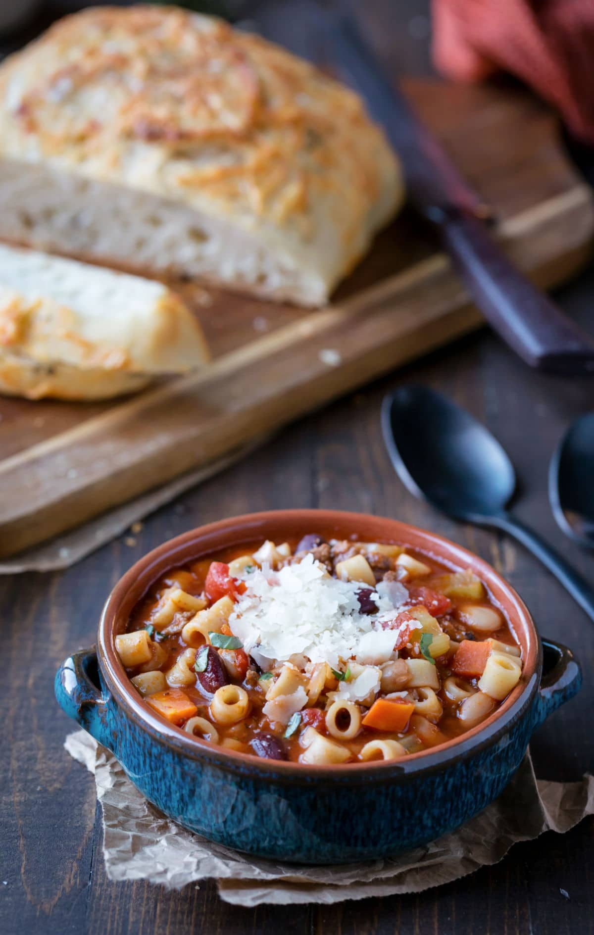 Bowl of pasta e fagioli soup next to a loaf of sliced bread