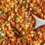 Wooden spoon stirring pasta e fagioli soup