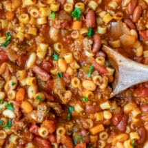 Wooden spoon stirring pasta e fagioli soup