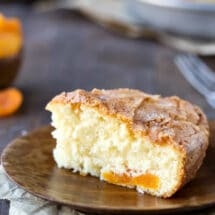 Slice of apricot cake on a wooden plate.