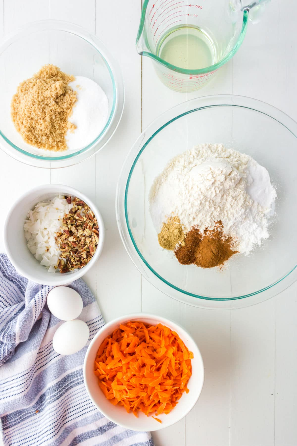 Carrot cake cookie ingredients in glass bowls.