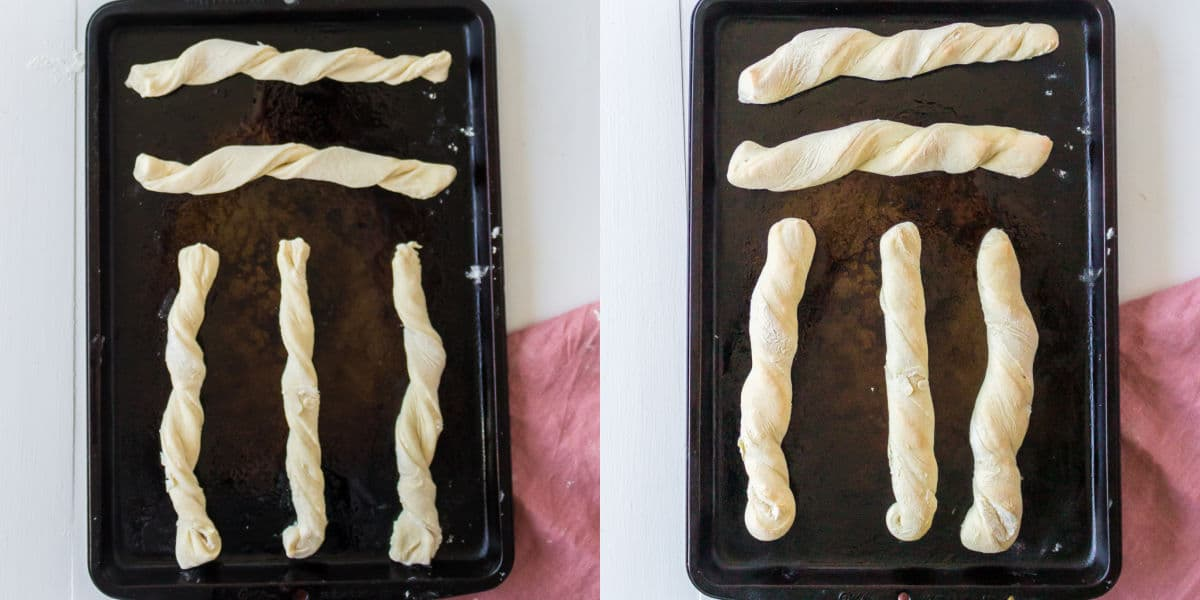 Baked and unbaked breadsticks on a metal baking pan.