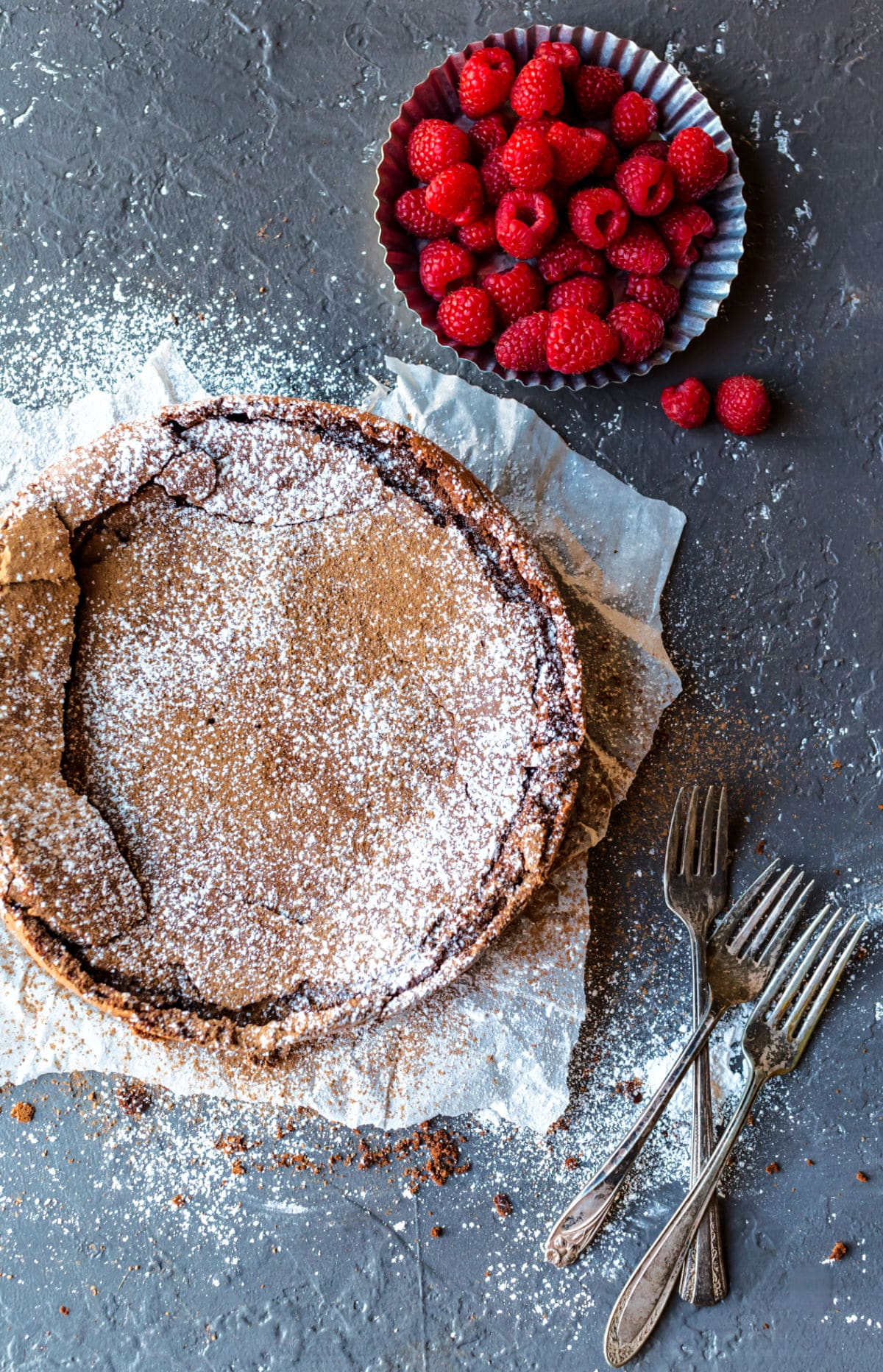 Flourless chocolate cake dusted with cocoa powder and powdered sugar.