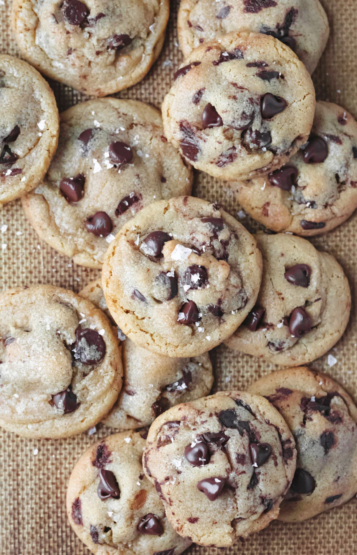 Stack of brown butter chocolate chip cookies topped with sea salt.