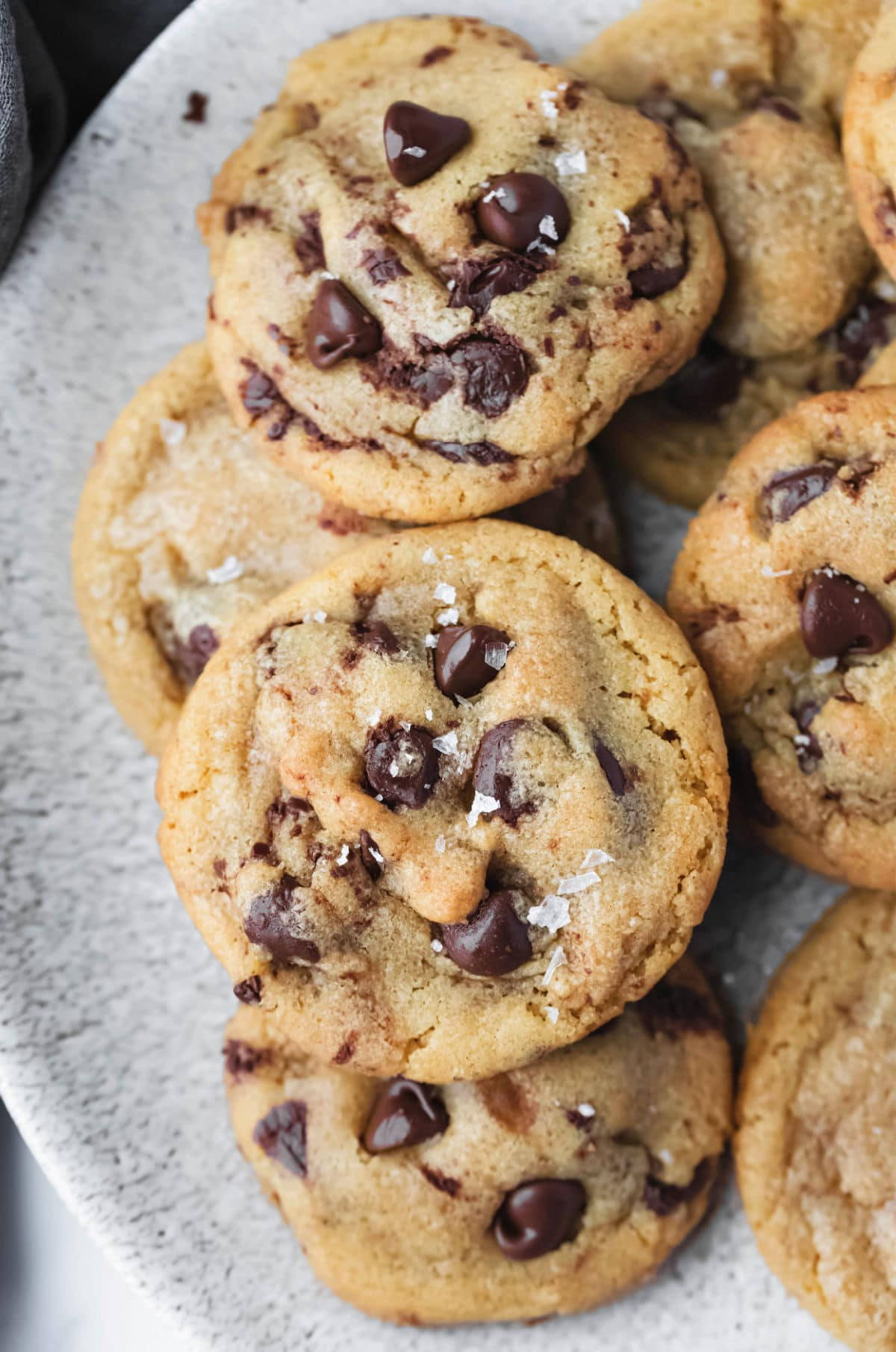 Brown butter chocolate chip cookies stacked on a plate.