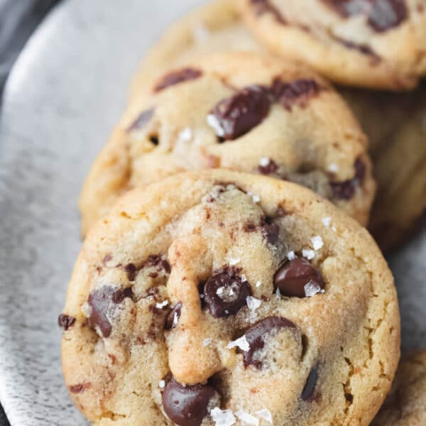 Brown butter chocolate chip cookies lined up on a plate.