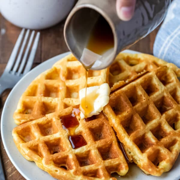 Pitcher pouring maple syrup into a plate of waffles.