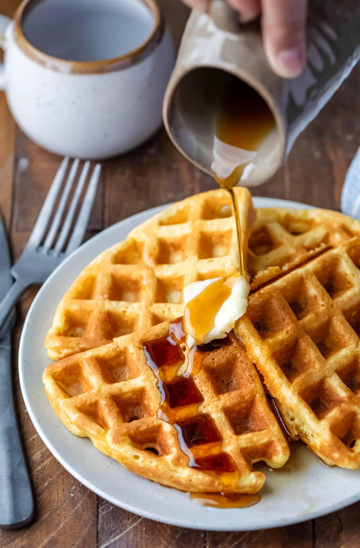 Syrup pouring onto a pat of butter on four waffles.