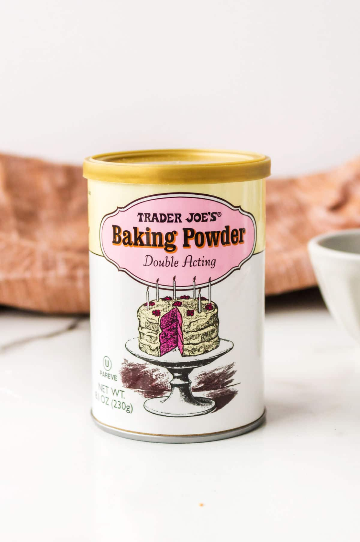 Can of baking powder next to a white bowl.