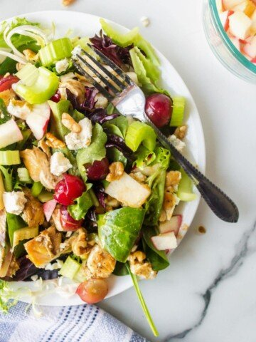 Waldorf salad on a white plate on a marble background