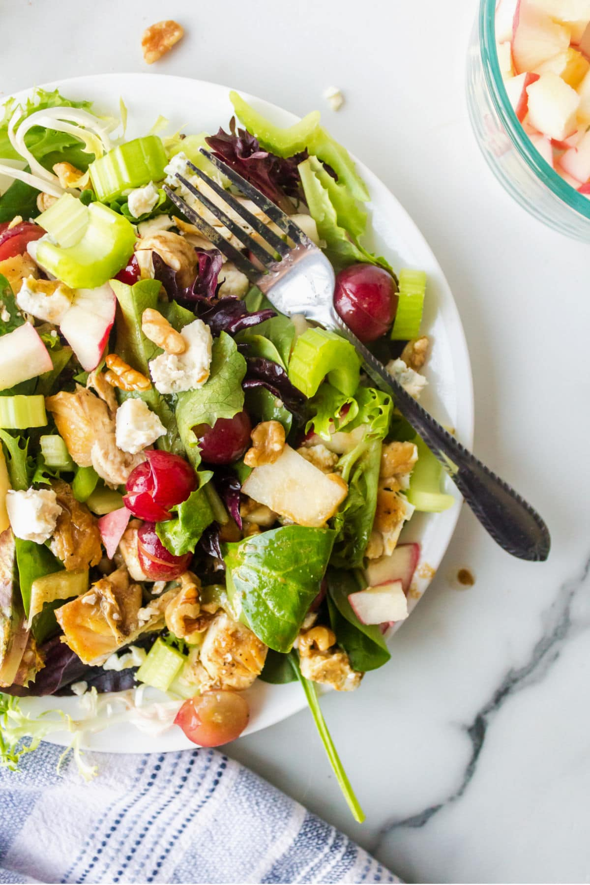 White plate with waldorf salad on a marble background.