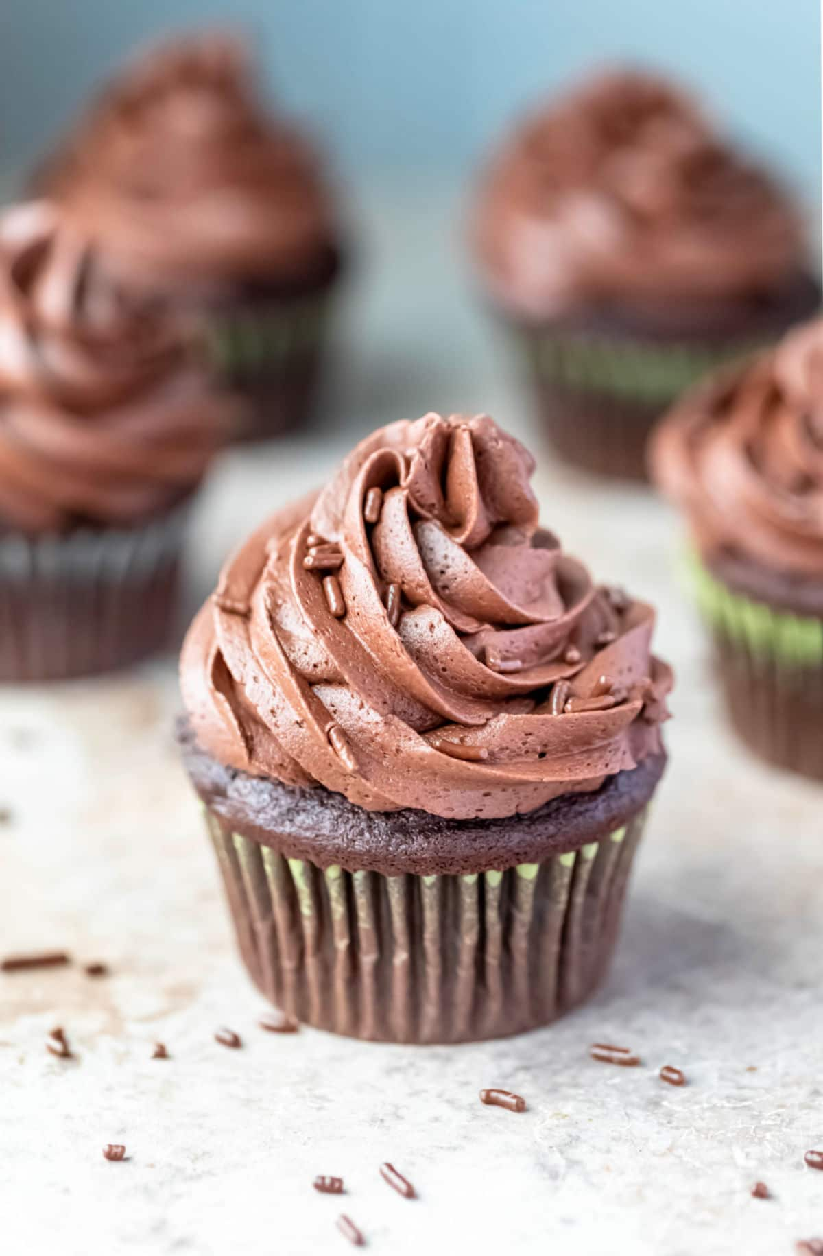 Five chocolate cupcakes topped with chocolate buttercream frosting.