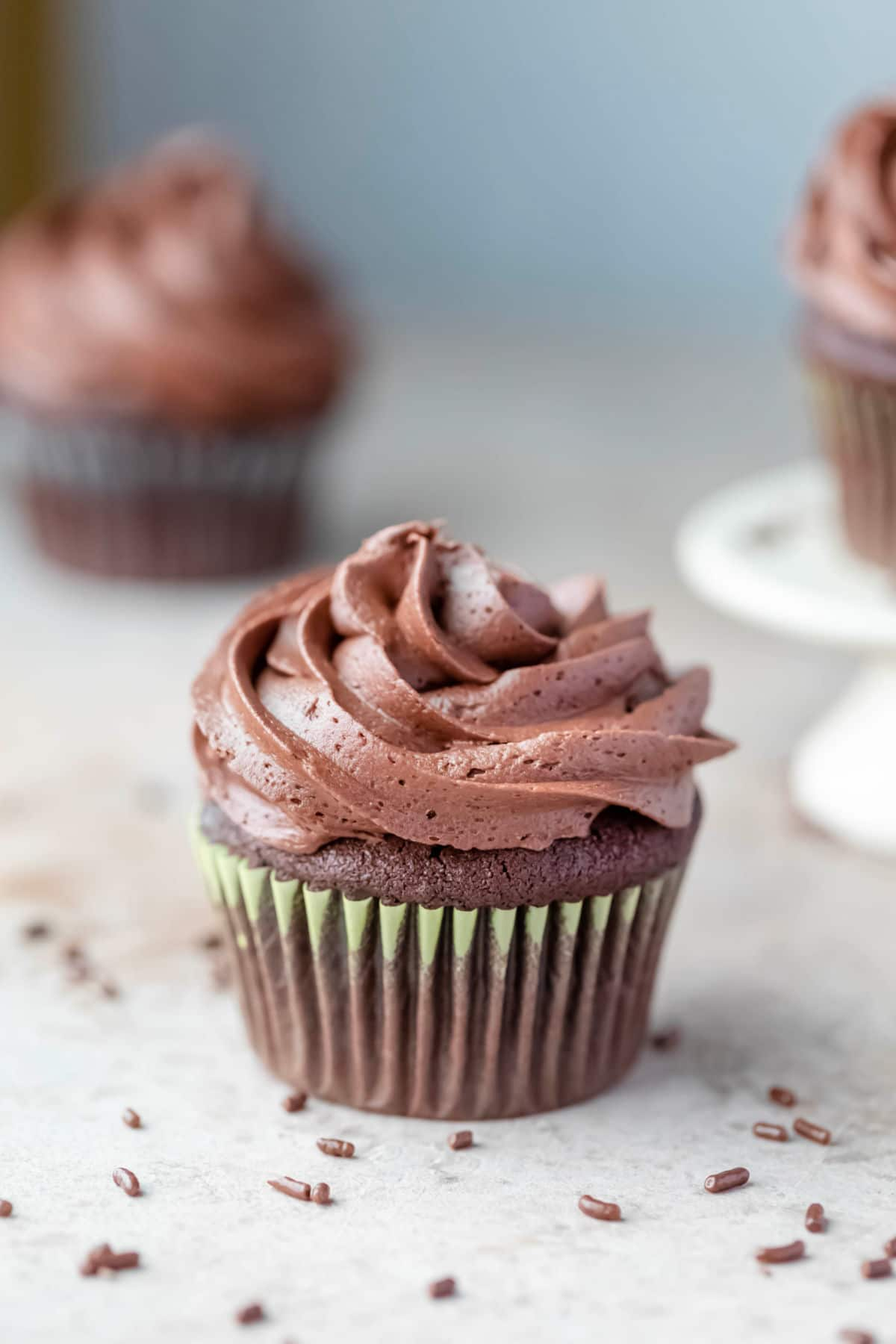 A chocolate cupcake topped with a low swirl of chocolate buttercream frosting.